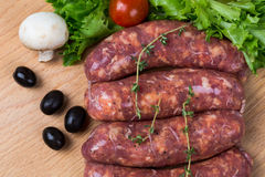 Uncooked raw sausages on wooden board. Uncooked raw sausages with lettuce, tomatoes, mushrooms on wooden board Royalty Free Stock Photography