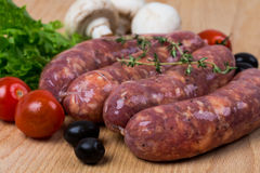 Uncooked raw sausages on wooden board Royalty Free Stock Photos
