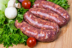 Uncooked raw sausages on wooden board. Uncooked raw sausages with lettuce, tomatoes, mushrooms on wooden board Stock Image