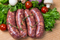 Uncooked raw sausages on wooden board. Uncooked raw sausages with lettuce, tomatoes, mushrooms on wooden board Royalty Free Stock Photo