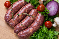 Uncooked raw sausages on wooden board Stock Images