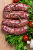 Uncooked raw sausages on wooden board. Uncooked raw sausages with lettuce, tomatoes, mushrooms on wooden board Royalty Free Stock Photos