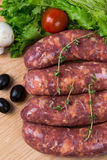 Uncooked raw sausages on wooden board. Uncooked raw sausages with lettuce, tomatoes, mushrooms on wooden board Stock Images