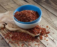 Uncooked Red rice in a bowl. On a wooden table Royalty Free Stock Images