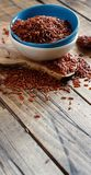 Uncooked Red rice in a bowl. On the wooden table Stock Photo