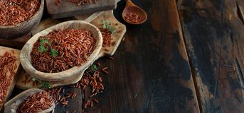 Uncooked Red rice in a bowl with a wooden spoon. On the table Royalty Free Stock Photo