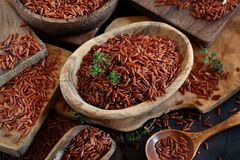 Uncooked Red rice in a bowl with a wooden spoon. On the table Stock Images