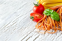 Uncooked red and white italian pasta with basil copy space. On wooden white background selective focus Stock Photos