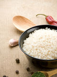 Uncooked rice in bowl. With spoon on wood background Stock Photos