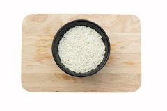 Uncooked rice in a bowl, on chopping block, isolated on white ba Stock Image