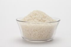 Uncooked rice in bowl with... Royalty Free Stock Images