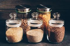 Uncooked rice, buckwheat, quinoa, macaroni, chickpeas in glass jars on a rustic table. Selective focus stock images