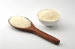 Uncooked rice, jasmine rice, mali rice,Thai jasmine rice in a wood ladle,white bowl ceramic on white background Stock Photo