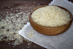 Uncooked rice in wooden plate. Uncooked rice with herbs in a wooden plate on linen napkin Royalty Free Stock Photography