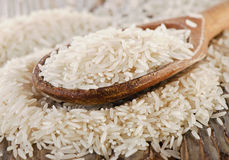 Uncooked rice in a wooden  spoon Royalty Free Stock Photo