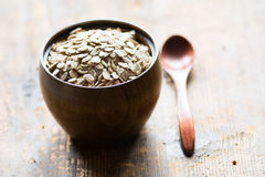 Uncooked rolled oats in wooden bowl Stock Photos