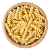 Uncooked rotini pasta in wooden bowl isolated on white background Stock Images