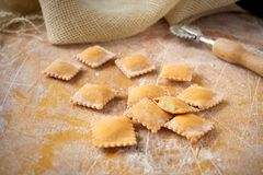 Uncooked rustic style ravioli orange color on a kitchen wooden table. Uncooked rustic style ravioli pasta with paprika orange color on a kitchen wooden table royalty free stock photos