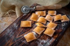 Uncooked rustic style ravioli orange color on a kitchen. Wooden table stock image
