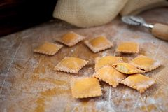 Uncooked rustic style ravioli orange color on a kitchen. Wooden table royalty free stock images