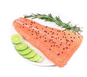 Uncooked salmon fillet with lime and herbs. Isolated on a white background Stock Photo