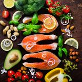 Uncooked salmon fish fillet with aromatic herbs, onion, avocado, broccoli, pepper bell, vegetables on wooden background royalty free stock images