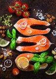 Uncooked salmon fish fillet with aromatic herbs, onion, avocado, broccoli, pepper bell, vegetables on wooden background royalty free stock photography