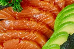 Uncooked salmon fish fillet with avocado, on marble plate, top view ingredients ready to eat. Uncooked salmon fish fillet with aromatic herbs, avocado, on marble stock photography