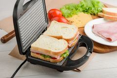 Uncooked sandwiches in panini press. Uncooked sandwiches in a panini press. Fresh vegetables, ham and cheese filling. Making of a tasty lunch stock photography