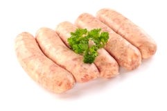Uncooked sausages with a leaf of parsley, on white background Royalty Free Stock Images