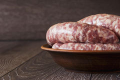 Uncooked sausages in a plate Royalty Free Stock Photos