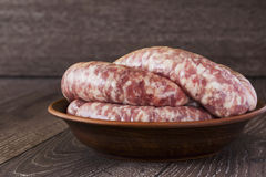 Uncooked sausages in a plate Royalty Free Stock Photography