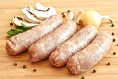 Uncooked sausages with vegetables Stock Image