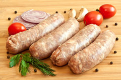 Uncooked sausages with vegetables Stock Photo