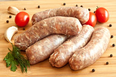 Uncooked sausages with vegetables Stock Images