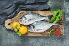 Uncooked sea bream or dorado fish with lemon. Fresh uncooked sea bream or dorado fish with lemon, herbs and spices on rustic wooden board over grey concrete Royalty Free Stock Image