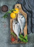 Uncooked sea bream fish with lemon, herbs, spices in bowls Stock Image
