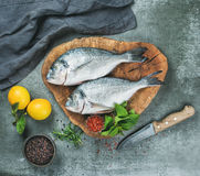 Uncooked sea bream fish with lemon, herbs, spices, grey background Royalty Free Stock Photography