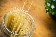 Uncooked spaghetti. Spaghetti in a glass container in a kitchen on a wooden table top Stock Image