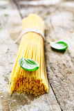 Uncooked spaghetti with basil. Bundle of uncooked spaghetti with basil for use in the kitchen to prepare fresh Italian pasta dishes Royalty Free Stock Photos
