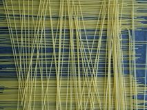 Uncooked spaghetti. Uncooked spaghetti on a blue table Stock Images