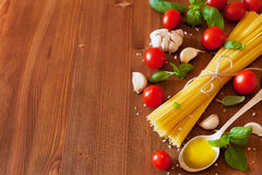 Uncooked spaghetti, cherry tomato, basil, garlic and olive oil, ingredients for cooking pasta, food background. Uncooked spaghetti, cherry tomato, basil, garlic Stock Images