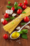 Uncooked spaghetti, cherry tomato, basil, garlic and olive oil, ingredients for cooking pasta, food background. Uncooked spaghetti, cherry tomato, basil, garlic Royalty Free Stock Image