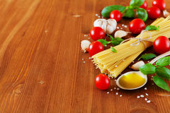 Uncooked spaghetti, cherry tomato, basil, garlic and olive oil, ingredients for cooking pasta, food background Stock Photography