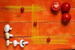 Uncooked spaghetti, cherry tomato, mushrooms on wooden background. Royalty Free Stock Photos