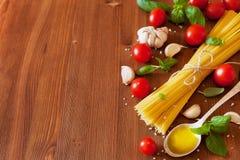 Uncooked spaghetti, czereśniowy pomidor, basil, czosnek i oliwa z oliwek, składniki dla kulinarnego makaronu, karmowy tło obrazy stock