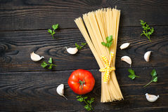 Uncooked spaghetti. On a dark wooden table. Top view Stock Photo