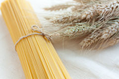Uncooked spaghetti and ears of ripe wheat. Pasta Stock Images