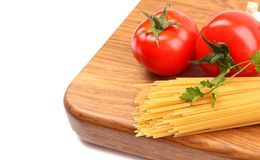 Uncooked spaghetti, garlic and tomatos. On a preparation board are located left Royalty Free Stock Photos