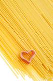 Uncooked spaghetti and heart. A pile of uncooked spaghetti with a heart-shaped pasta Stock Image
